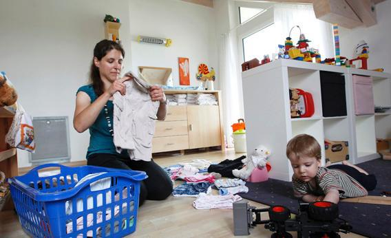 Claudia folds clothes in the playroom next to son Michael at home in Durach, southern Germany.
