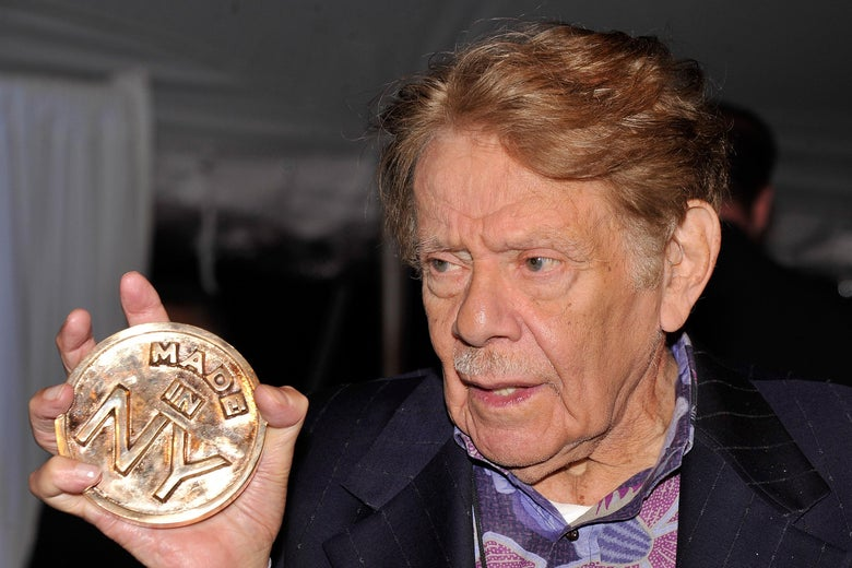 "Jerry Stiller holding a large metal coin that says ""Made in NY"" on it"
