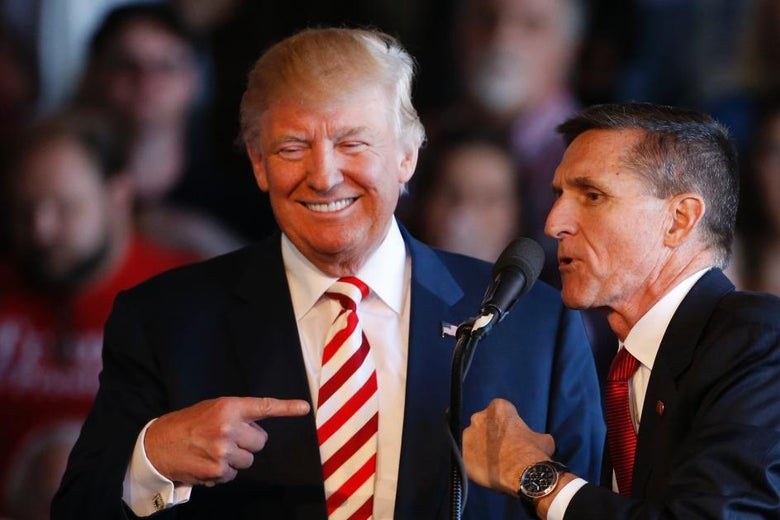 Michael Flynn leans toward Donald Trump to speak into a microphone.