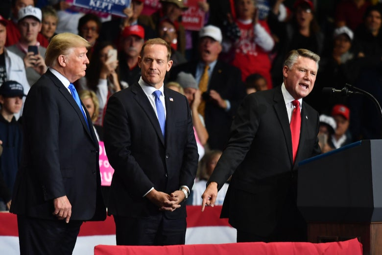 Mark Harris speaks as GOP Rep. Ted Budd and Donald Trump look on at a campaign rally in North Carolina.
