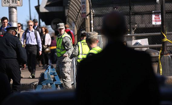 People walk to work by National Guardsman near the scene of twin bombings at the Boston Marathon on April 17, 2013 in Boston, Massachusetts.