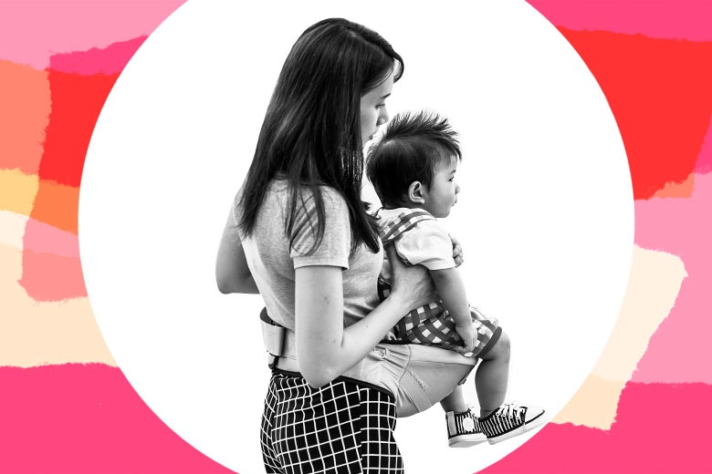 Woman standing with a child in a baby carrier.