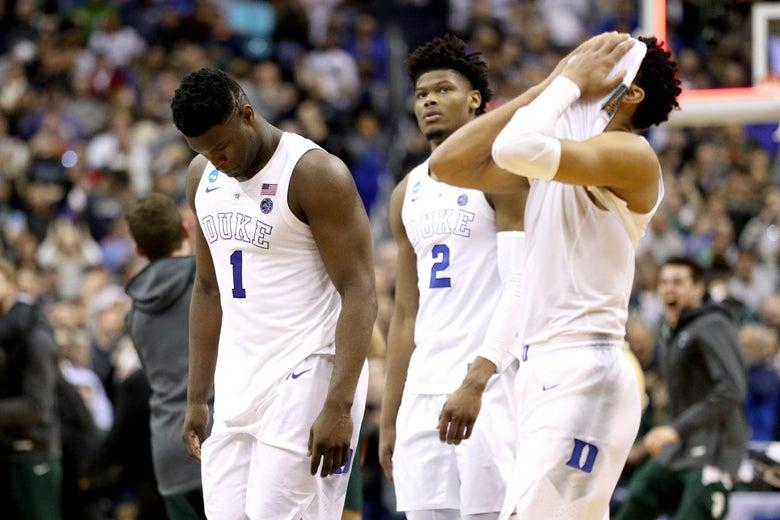 Zion Williamson, Cam Reddish, and Tre Jones looking sad, hanging their heads, in their Duke uniforms