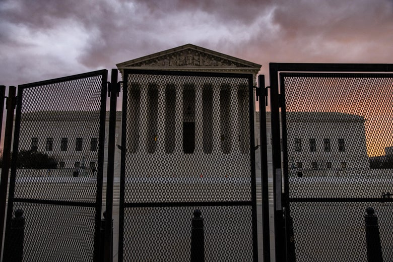 The Supreme Court at dusk, with a large fence around the building.