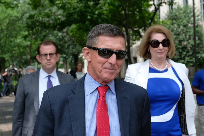 Michael Flynn, in sunglasses and a suit, walks with two people behind him.