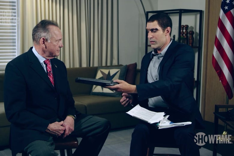 Roy Moore sits in a chair while Sacha Baron Cohen, wearing a ridiculous, lantern-jawed disguise, waves a metal-detector over him.