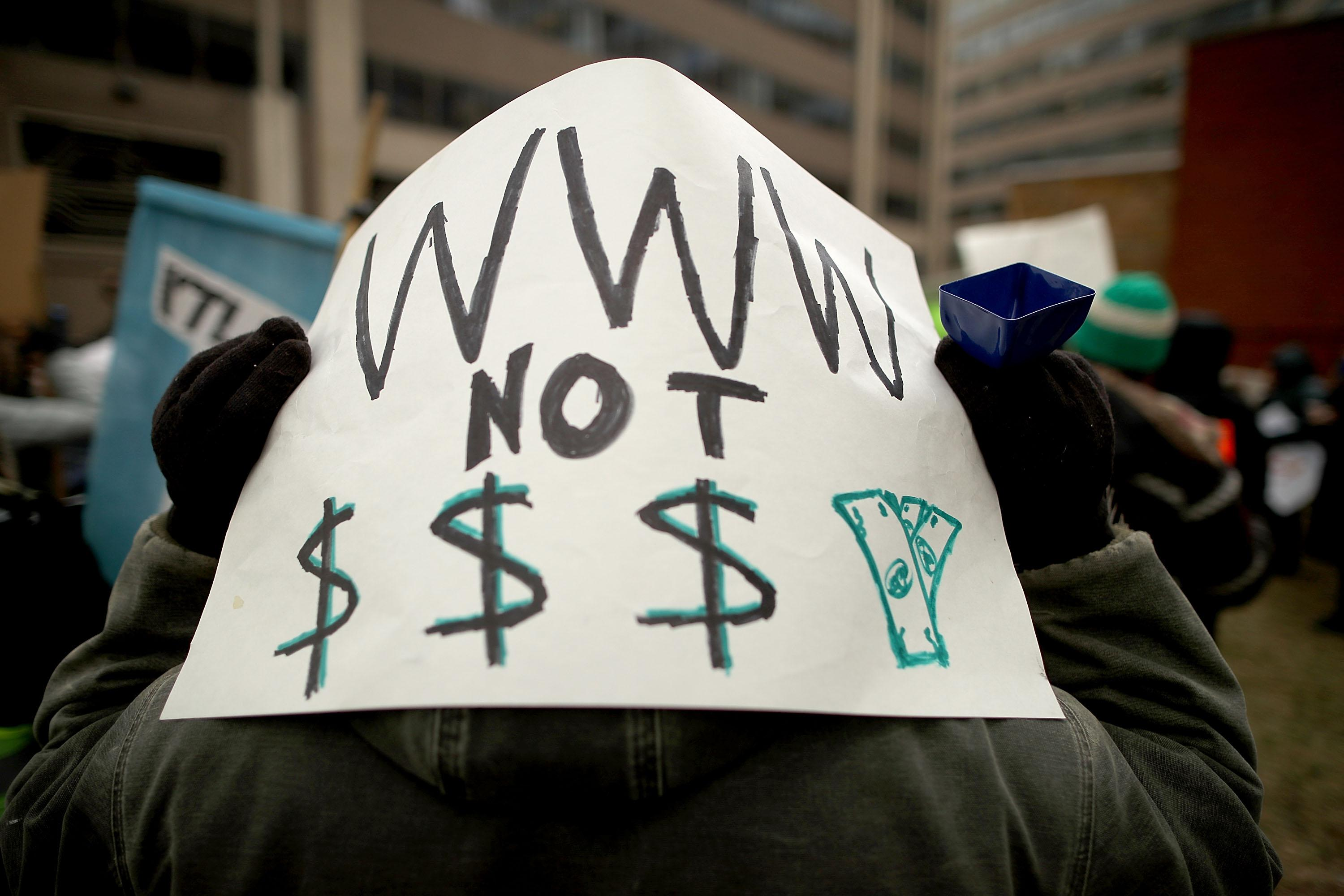 "A protest sign reads, ""WWW not $$$."""