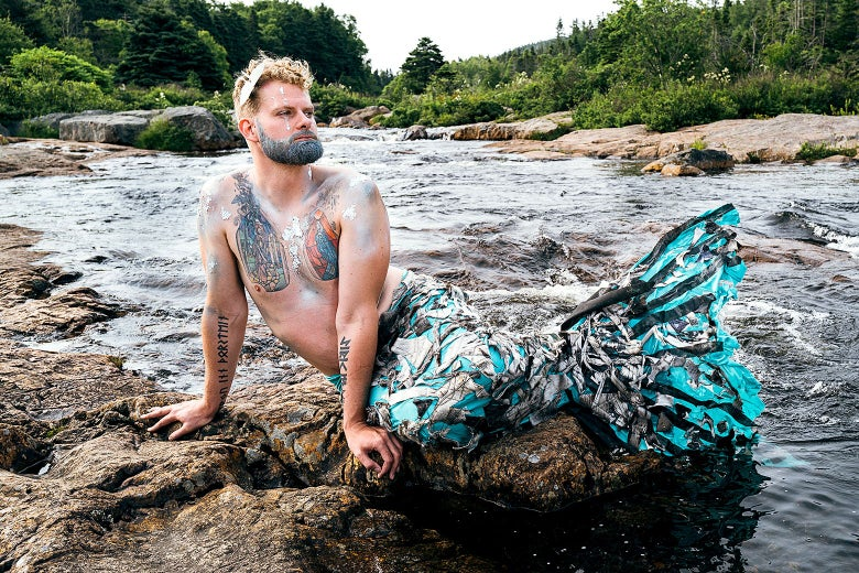 A merman with a blue tail and glittery makeup basks on a rock.
