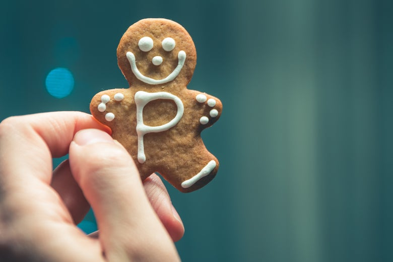 A hand holds up a gingerbread human-shaped cookie with the letter P on its torso.