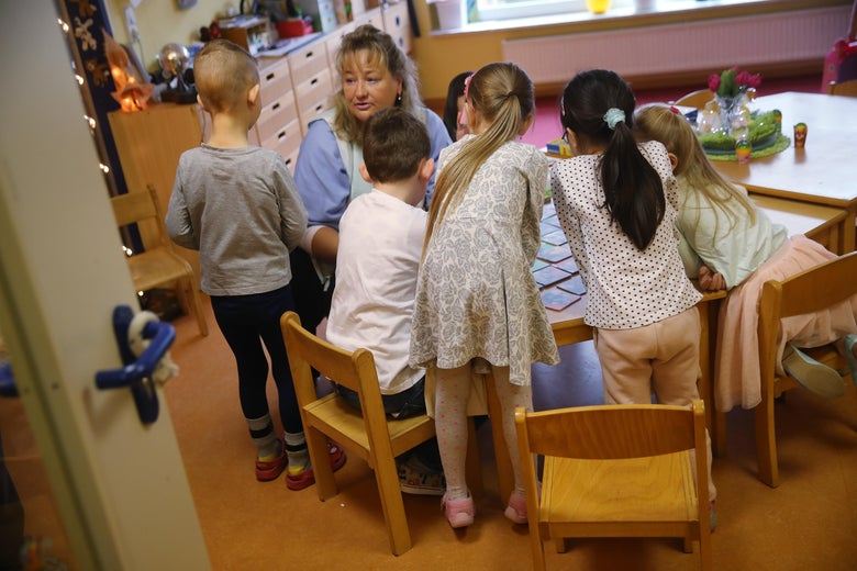 A nursery school teacher supervises children in a day care center with tables and toys.