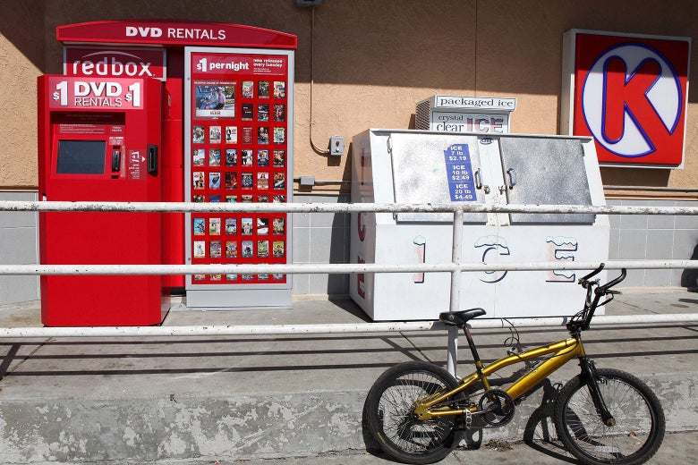 A RedBox video rental kiosk in front of a gas station. A yellow bike is parked nearby.