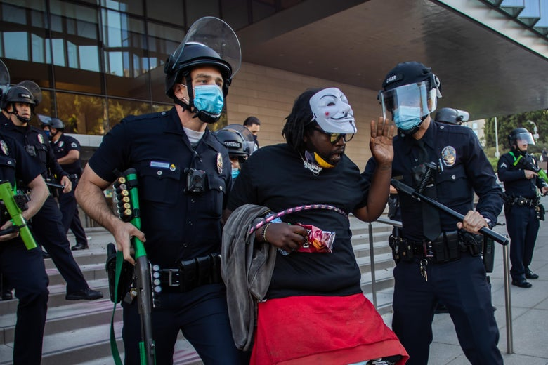 Cops with helmets and batons drag a man from courthouse steps, where other cops are arranged.