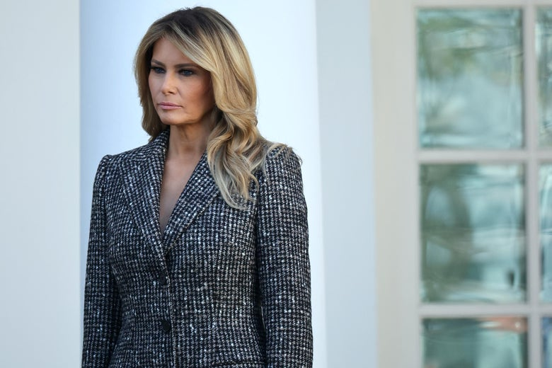 Melania Trump stands outside the White House in a gray patterned peacoat.