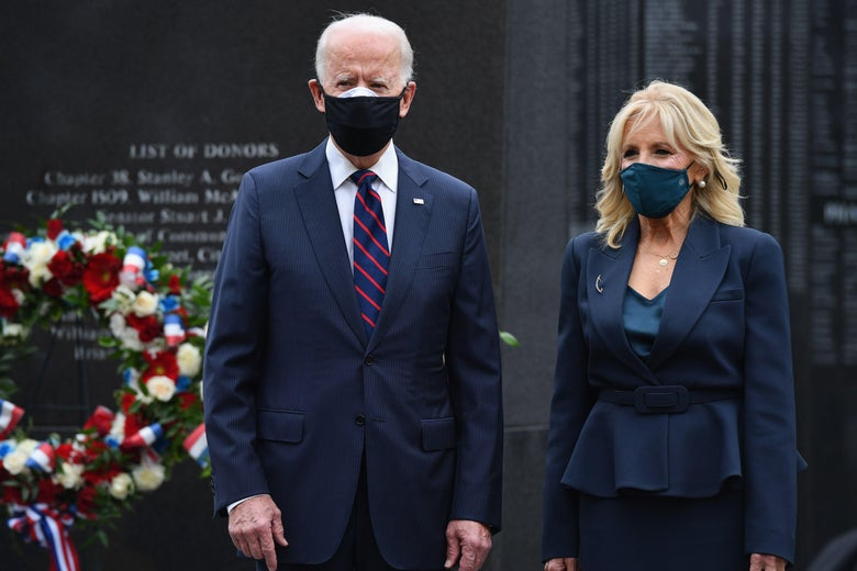 The pair wear black masks in front of a stone memorial.