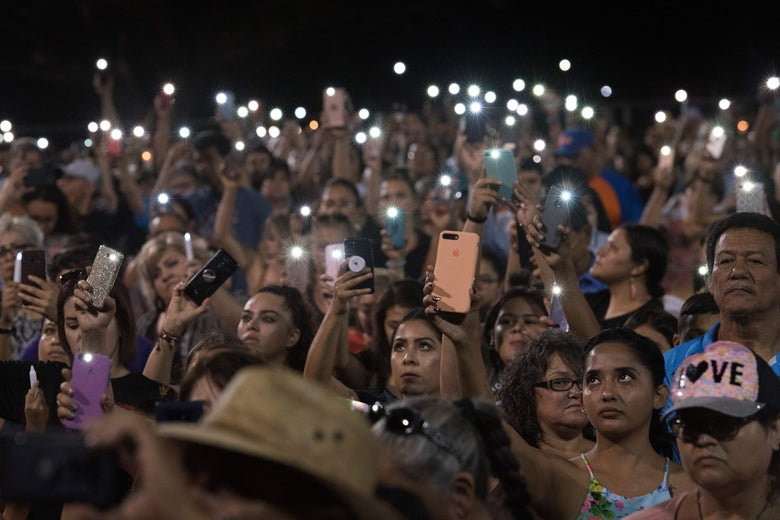 People hold up their phones during a vigil.