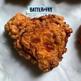 A cooked, battered chicken thigh labeled Batter + Fry.