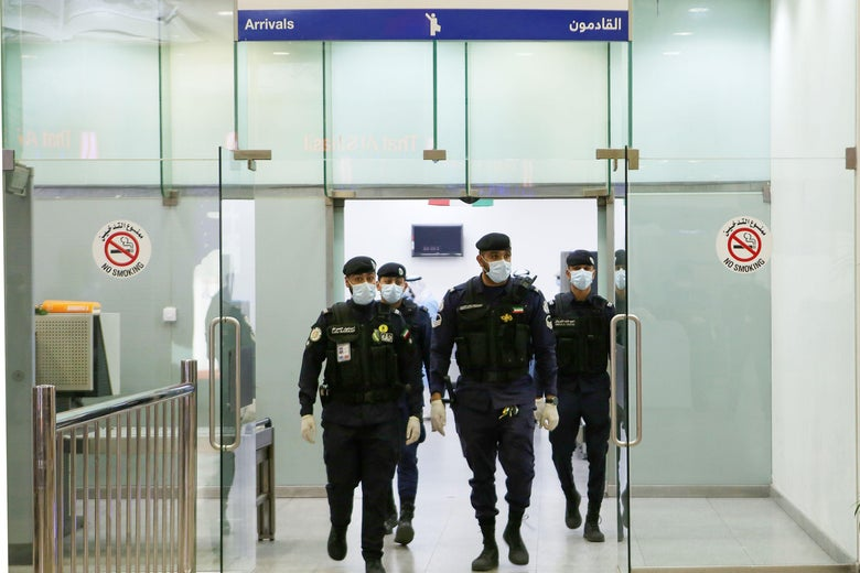 Kuwaiti policemen wearing protective masks wait at Sheikh Saad Airport in Kuwait City, on February 22, 2020, before transferring Kuwaitis arriving from Iran to a hospital to be tested for coronavirus.