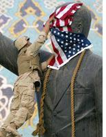 A Marine drapes the flag over a statue of Saddam Hussein. Click image to expand.