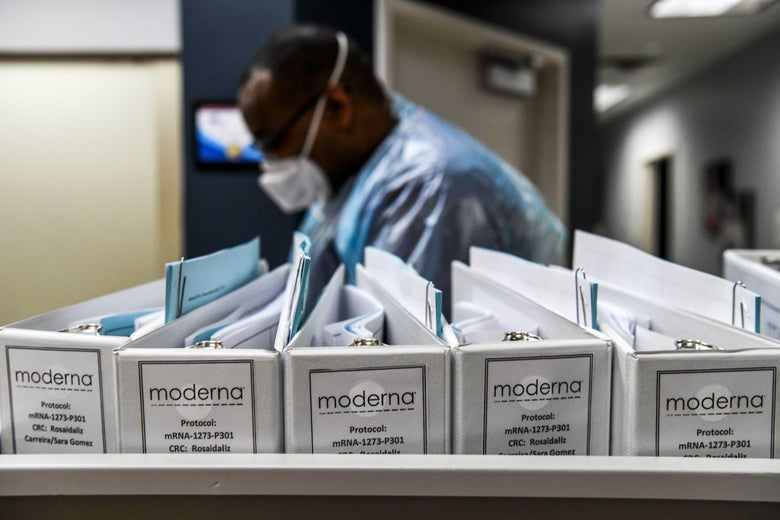 """Folders labeled """"Moderna"""" are seen in front of a person wearing PPE."""