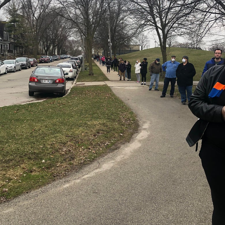 A long line of people stretches down a street.
