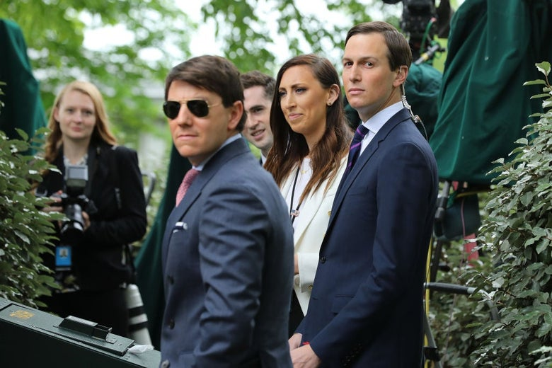 Gidley, Kushner, and three others stand among shrubs on the White House grounds.