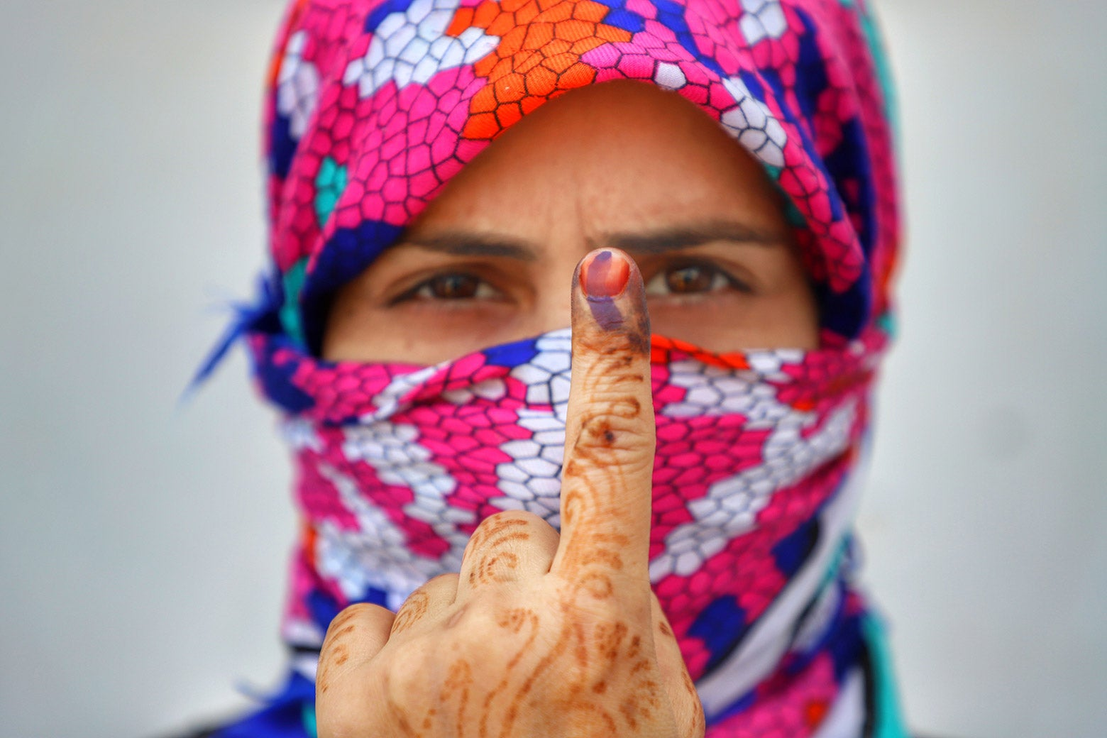 A woman in bright headscarf holds up her inked index finger after casting her vote during the first phase of general elections in the state of Uttar Pradesh, India, on Thursday.