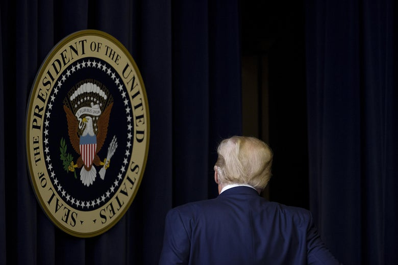 Trump, seen from the back, walking past the presidential seal hanging in front of a curtain