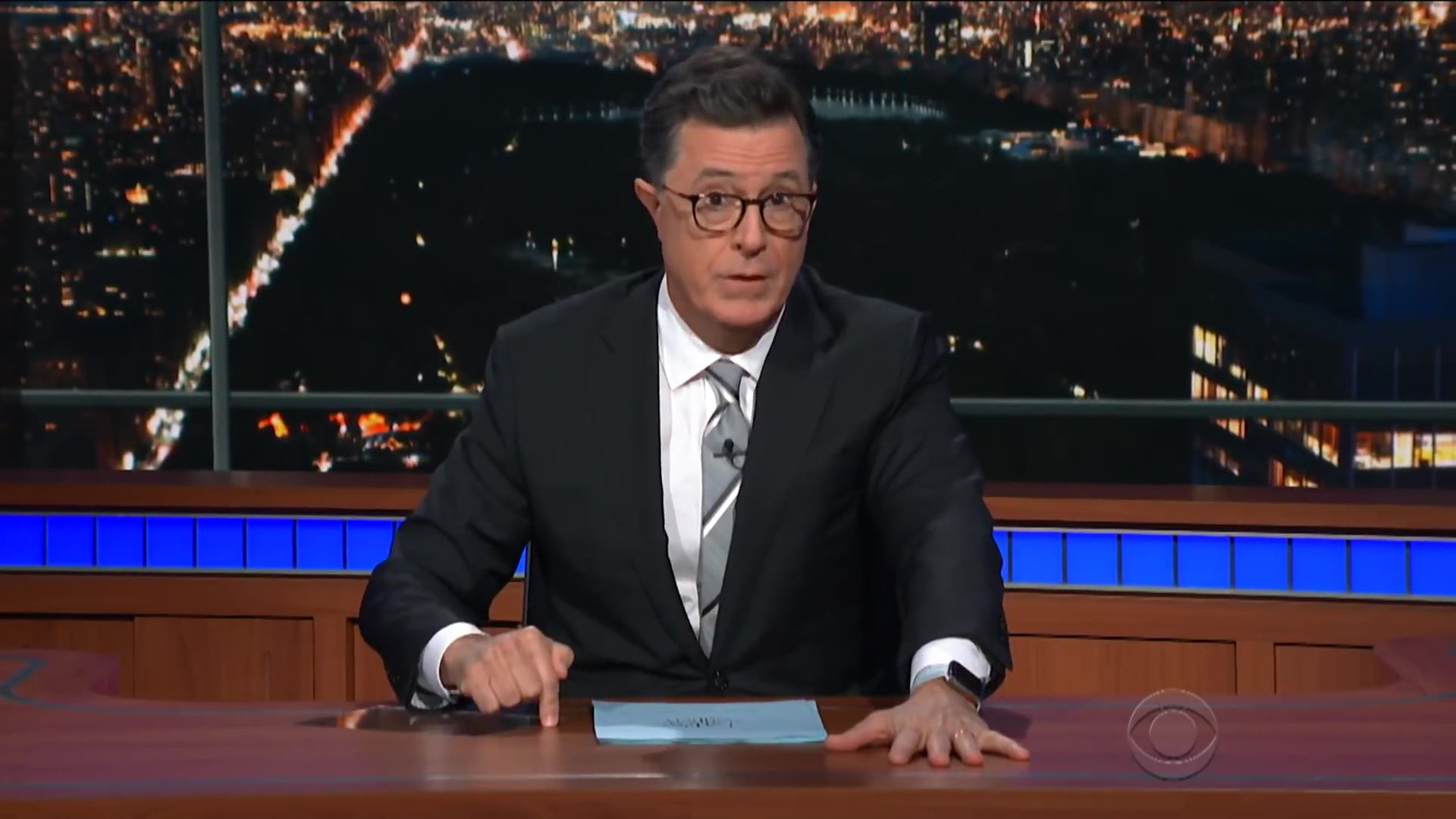 Stephen Colbert sitting behind a desk.
