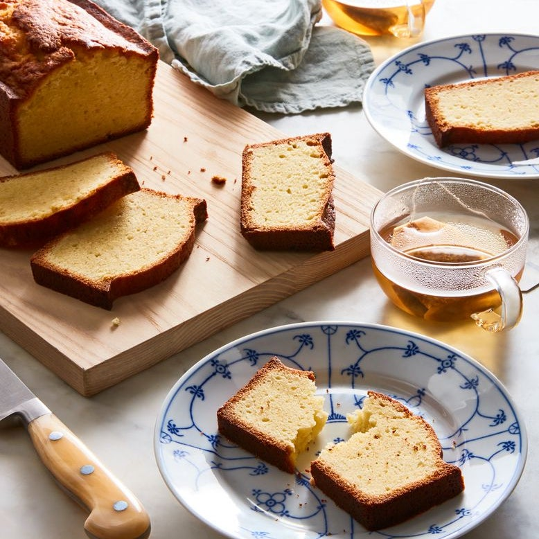 A loaf of plain pound cake sliced on a wooden cutting board, surrounded by individual slices of pound cake on small plates, two glass cups of tea, and a knife.