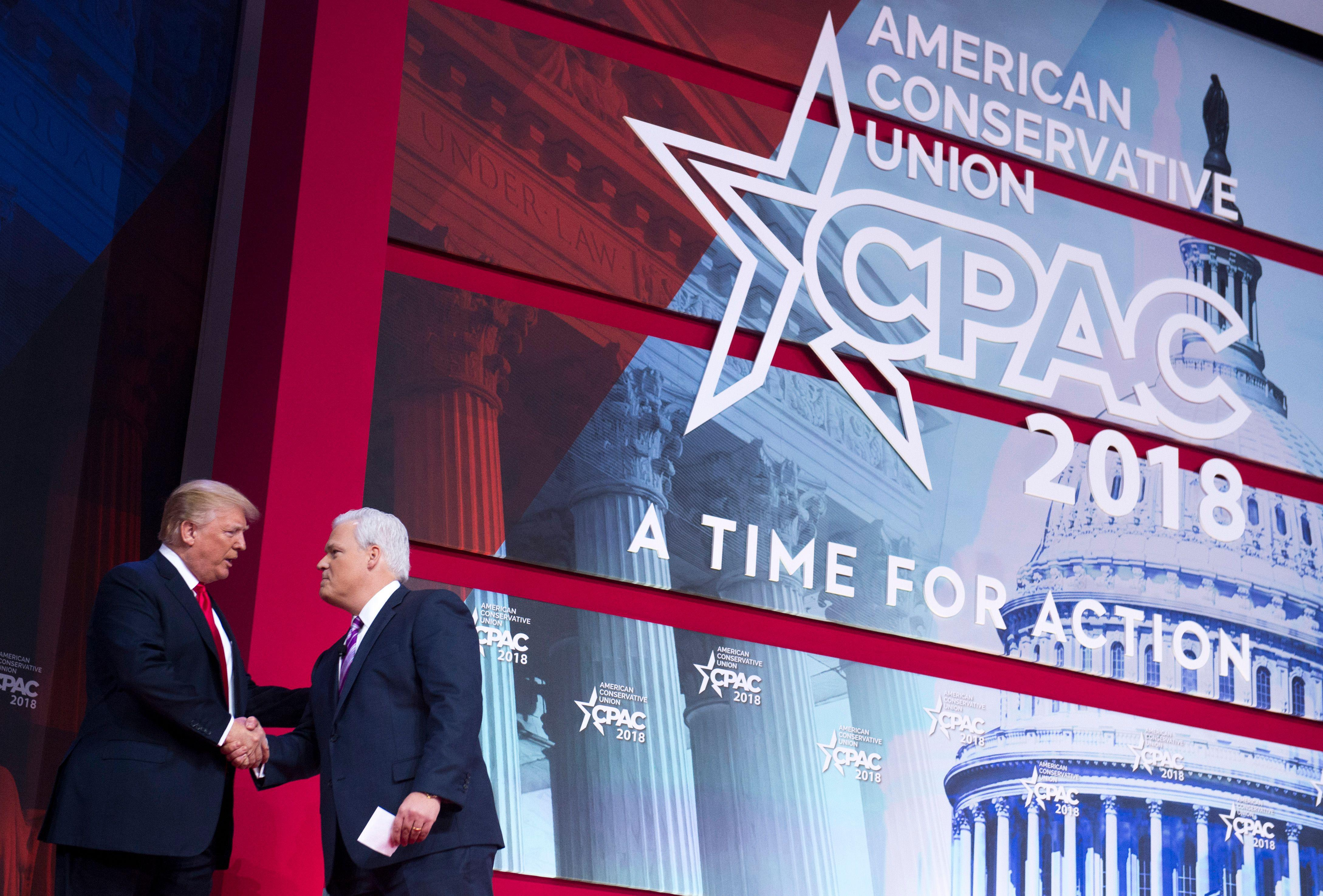 US President Donald Trump shakes hands with Matt Schlapp, chairman of the American Conservative Union, during the 2018 Conservative Political Action Conference (CPAC) at National Harbor in Oxon Hill, Maryland, February 23, 2018. / AFP PHOTO / SAUL LOEB        (Photo credit should read SAUL LOEB/AFP/Getty Images)