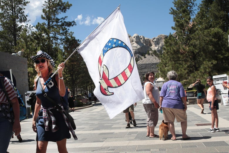 "A person wearing blue and a cowboy hat walks while holding a white flag with the letter ""Q."" In the background Mount Rushmore is visible."