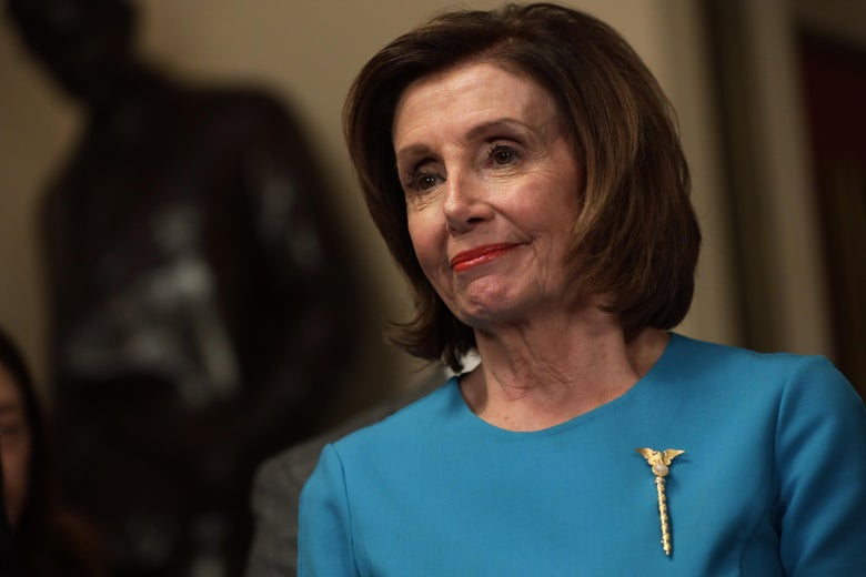 Nancy Pelosi in a blue dress with a gold pin.