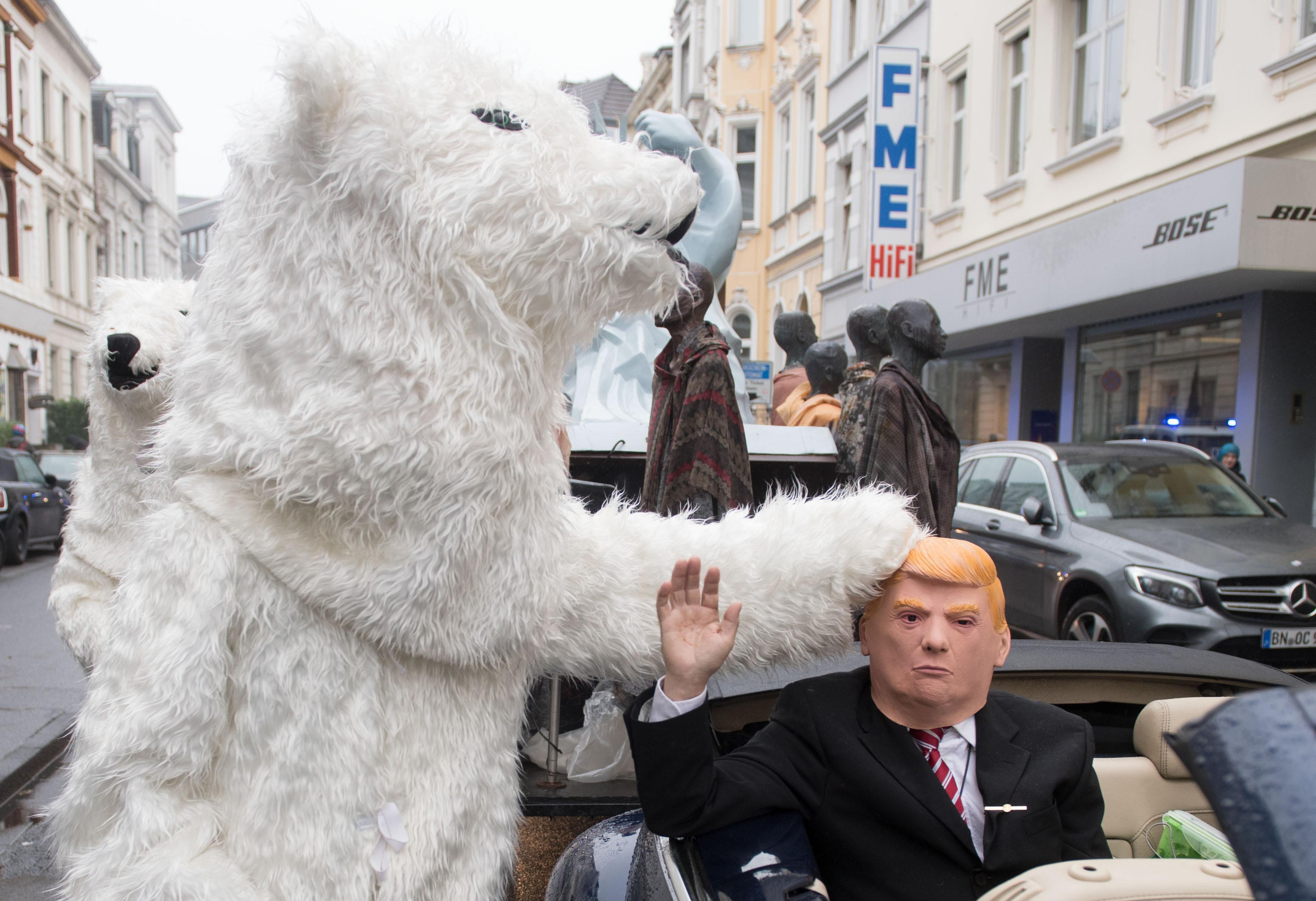 A demonstrator dressed as Donald Trump parades with other activists dressed as polar bears