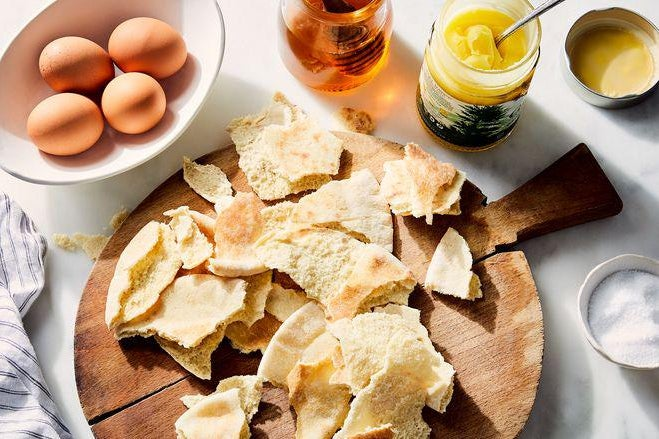 Broken up pieces of dry pita bread on a circular wooden cutting board with nearby ingredients, including eggs and honey.