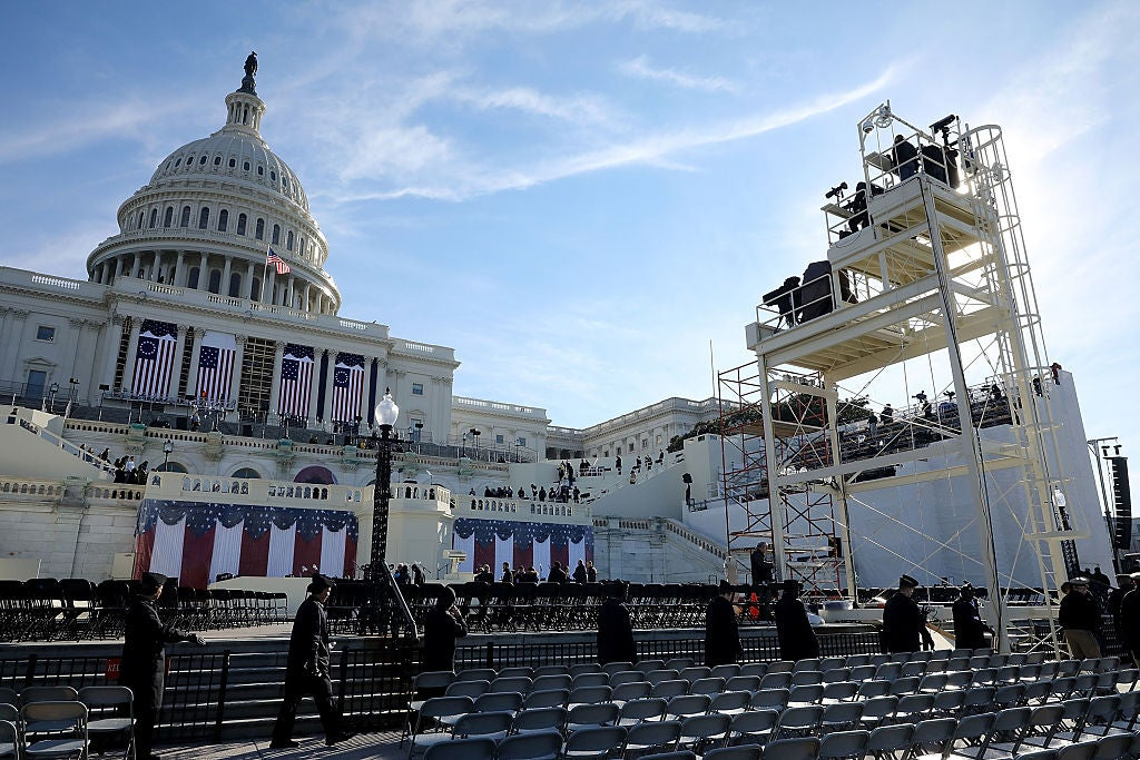 Workers install scaffolding and seats outside the U.S. Capitol building.
