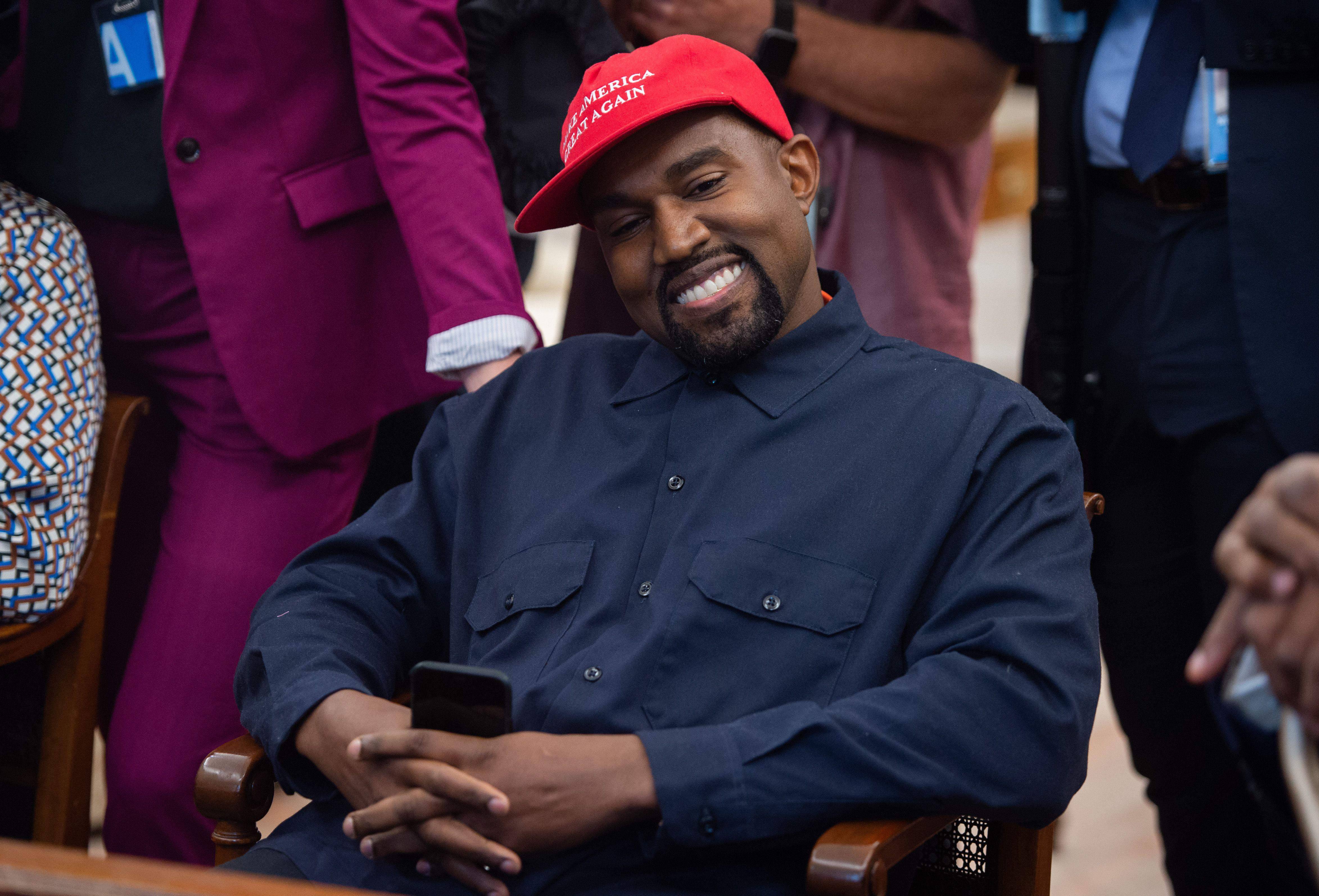 Kanye West in the Oval Office with his phone in his hands.