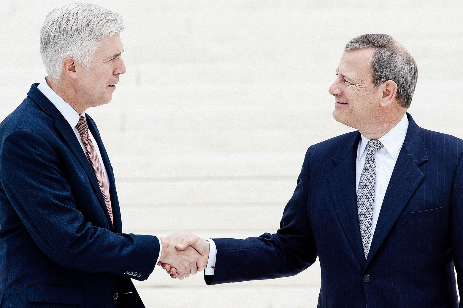 Neil Gorsuch shakes hands with John Roberts.