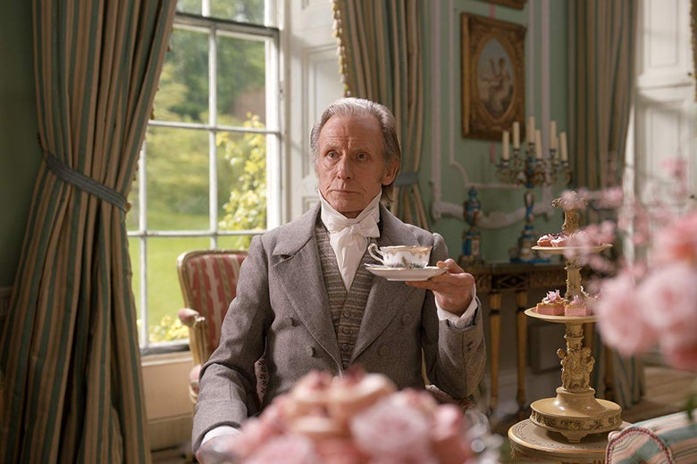 Bill Nighy sits in a lavishly furnished room holding a cup of tea in a saucer. A nearby table is covered in towers of pink desserts.