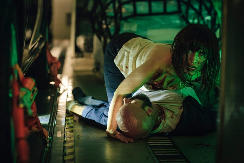 a woman crouches above a prone man's body