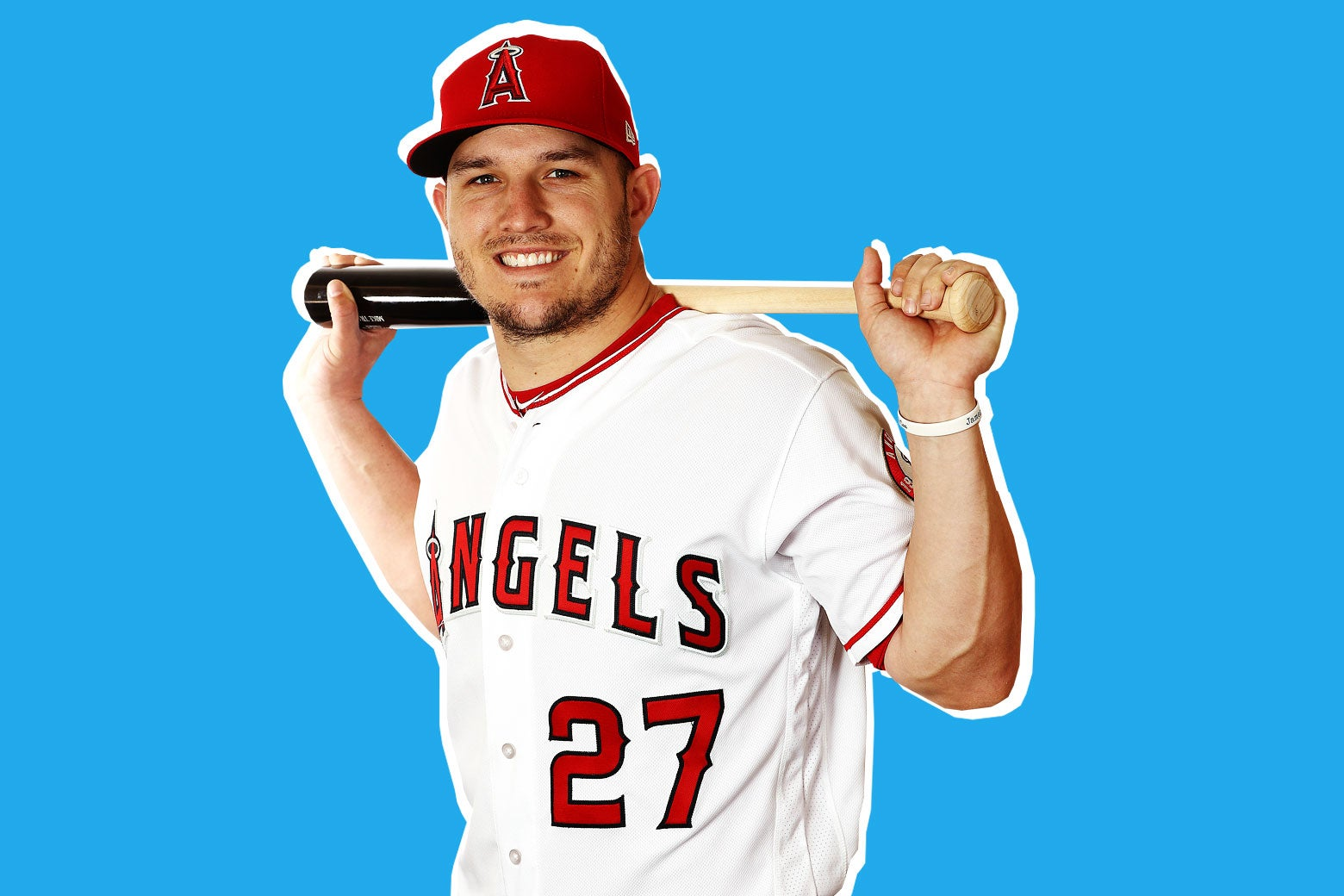 Photo illustration of Mike Trout, No. 27 for the Los Angeles Angels, posing with a baseball bat slung over the back of his shoulders while he smiles winningly at the camera.