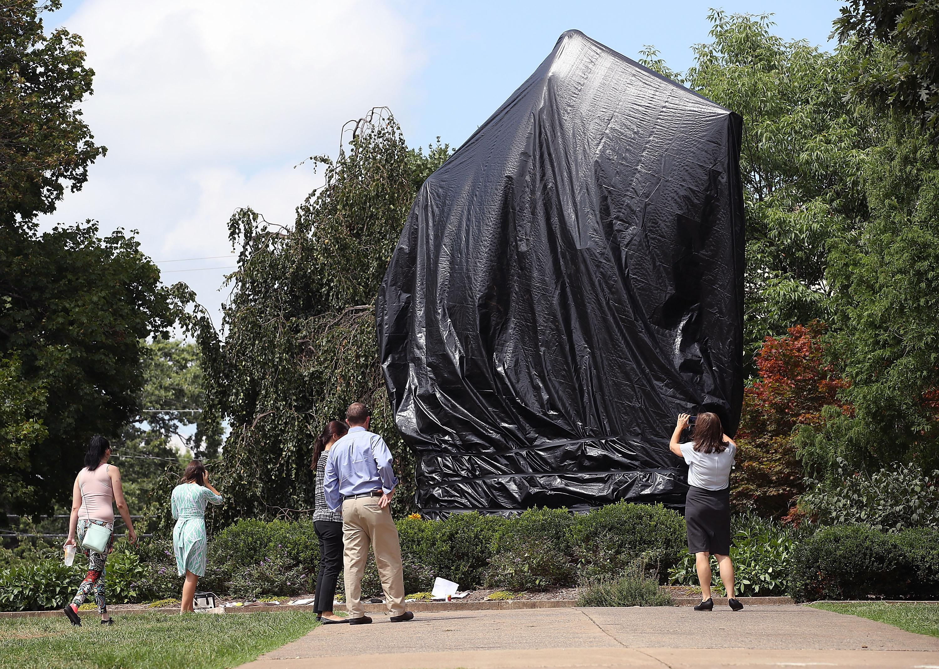 The statue of Confederate Gen. Robert E. Lee covered with a black tarp.