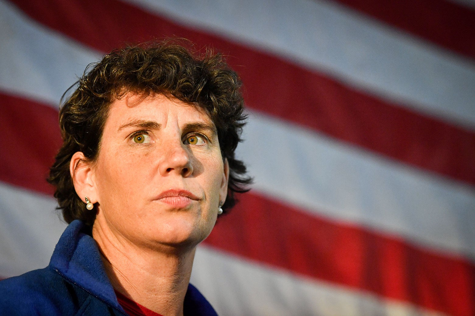 Amy McGrath stands in front of an American flag.