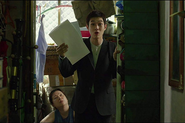 A still from Parasite showing actor Choi Woo-shik holding up two sheets of paper excitedly.