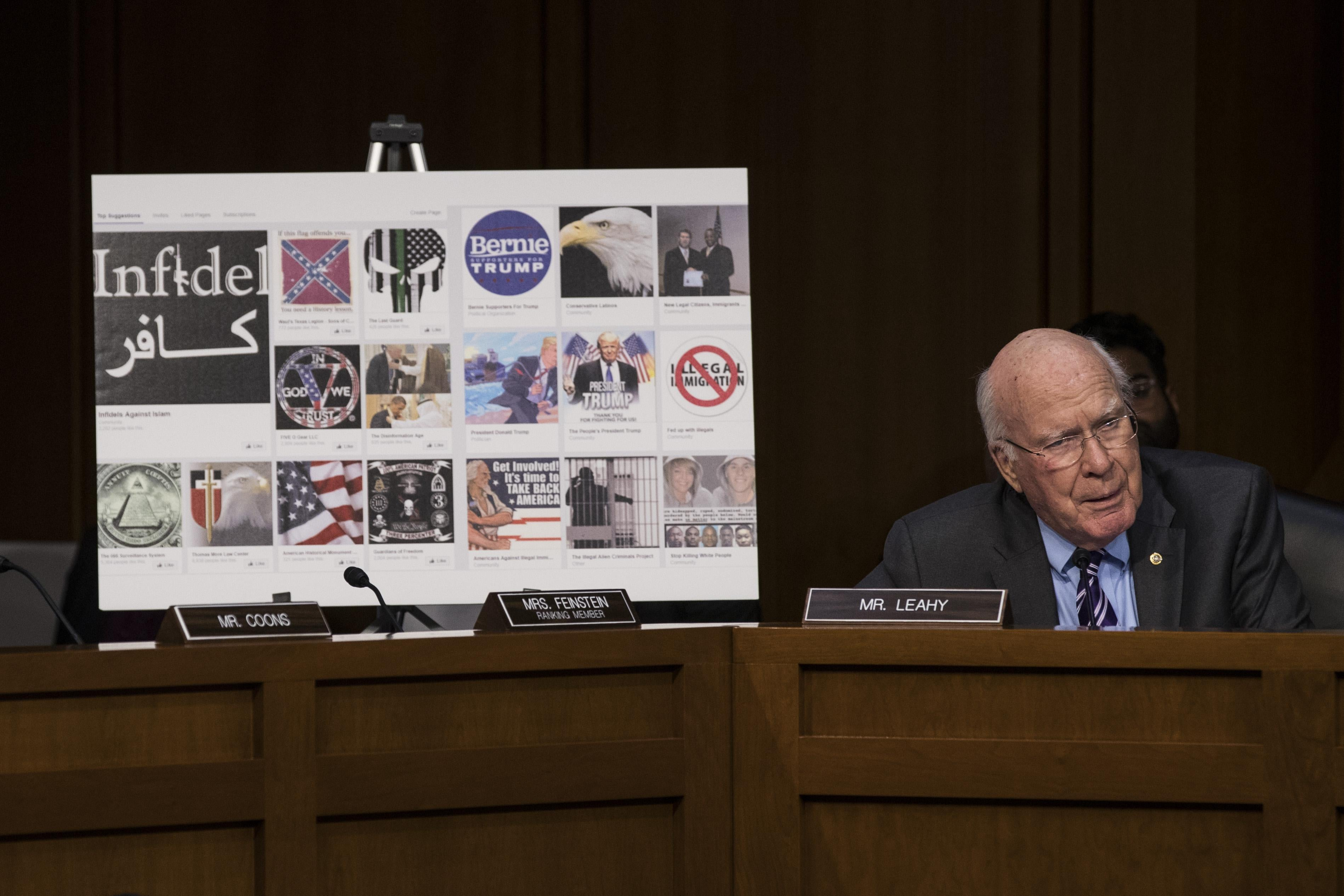 Sen. Patrick Leahy sits in a committee room next to a poster board showing several examples of Russian-created Facebook pages.
