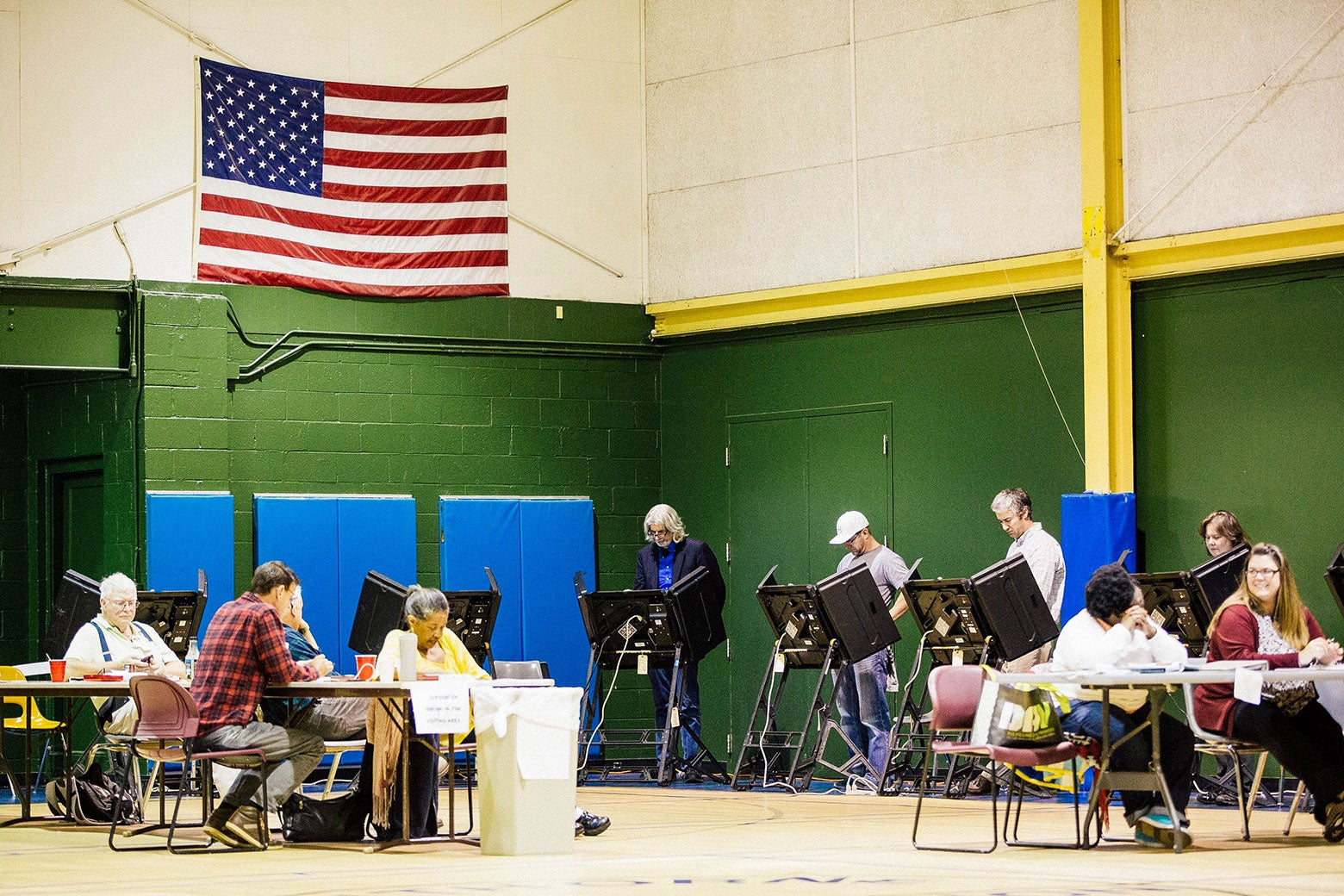 Voters stand behind electronic machines in a rec center gym.