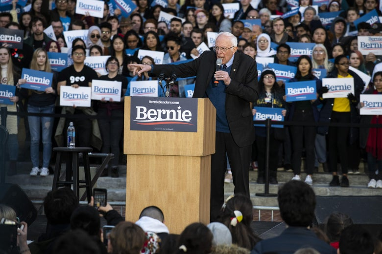 Bernie Sanders speaks at a podium with a crowd of supporters surrounding him.