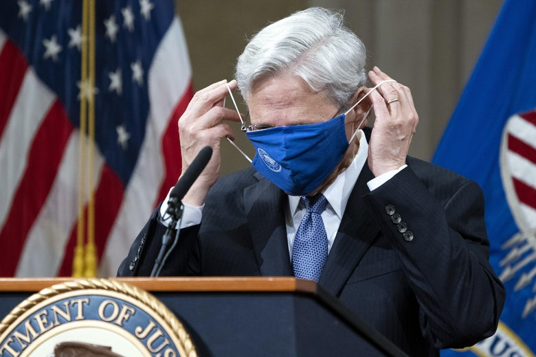 U.S. Attorney General Merrick Garland adjusts his face mask, which is covering his eyes, nose, and mouth, as he stands at a lectern.
