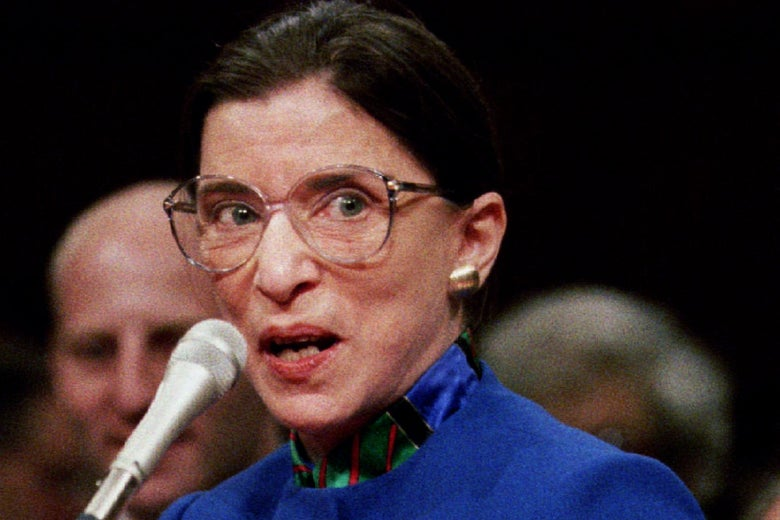 Ruth Bader Ginsburg behind a microphone in big glasses and a blue jacket.