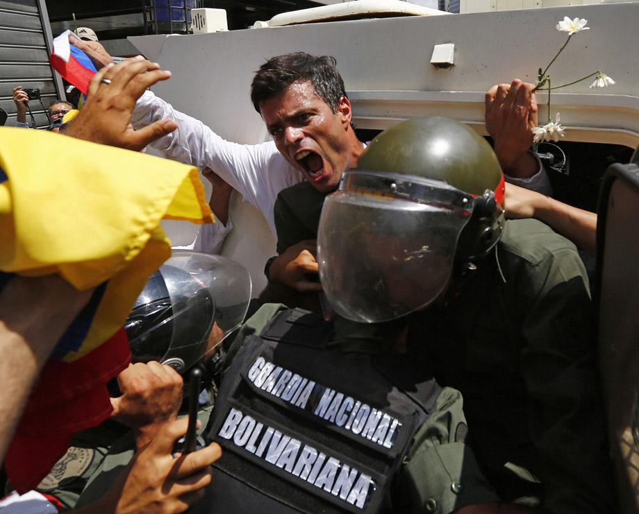 Venezuelan opposition leader Leopoldo Lopez gets into a National Guard armored vehicle in Caracas February 18, 2014. Lopez, wanted on charges of fomenting deadly violence, handed himself over to security forces on Tuesday.