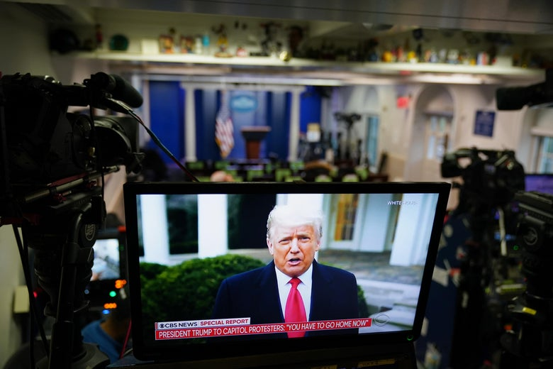 A TV screen at the rear of the White House press room shows Donald Trump speaking.